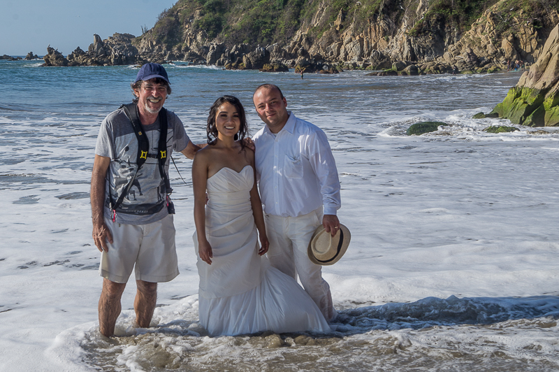 Carlos Ramos Photographer at La Bocana Beach in Huatulco, Oaxaca Mexico with Alicia and Alberto, two days after their weeding in Hatulco. Picture taken during the trash the dress session.